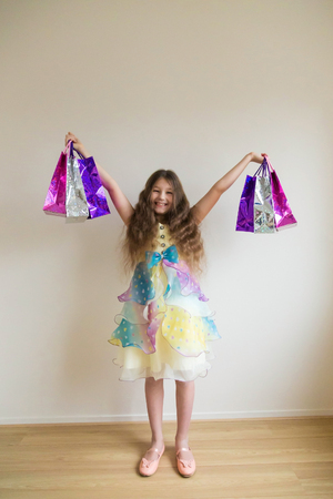 Fashion smiling little girl with shopping bags and gifts. Happy child holds a lot of gifts. Sale, holidays, fashion, shopping, family shopping concept.