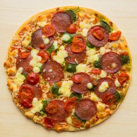 Baked pizza salami mozzarella pesto. Pizza as a food background or texture.  Italian fast food, prepack, half-stuff. Fast and junk food concept