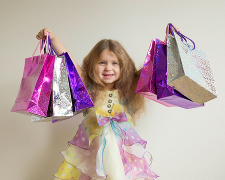 Fashion girls shopping. Beautiful smiling little girl with shopping bags and gifts. Happy child holds a lot of gifts. Sale, holidays, fashion, shopping concept.  Stock Photo