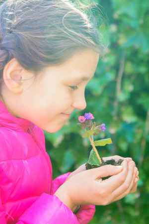 The child is holding a young flower growing in the ground. The child is going to plant this flower. The child smells a flower and smiles. Green planet Earth, ecology, caring for plants concept. Standard-Bild - 99373991