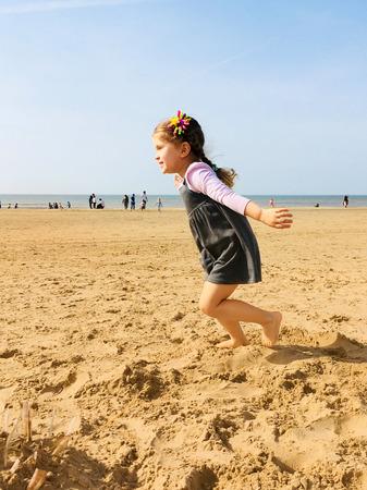 Ein kleines glückliches kleines Mädchen läuft barfuß entlang den Strand in Richtung der Sonne . Ein Kind , der Arme angehoben . Flügel wie Grab . Glück Konzept Bild Standard-Bild - 99627063