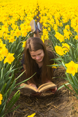 Happy young teenager girl reads book among flowers. Adorable teenager girl having fun in flowering daffodil fields. Happiness, youth, spring, education, achievements, study, pleasure concept. Standard-Bild - 99983893