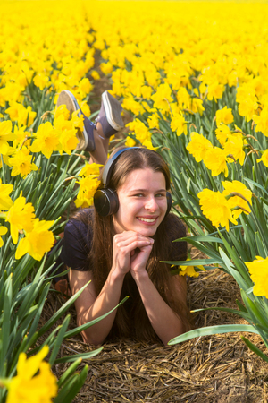 Teen girl listening to music on headphones. A young girl on a day off rests outside the city, on flower fields. Youth, spring, happiness, joy concept. Standard-Bild - 99995959