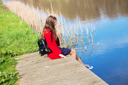 Lonely young teenage girl sitting on the river bank. Youth, sadness, loneliness, reflections concept. A young cute girl is resting and dreaming. Standard-Bild - 99983894