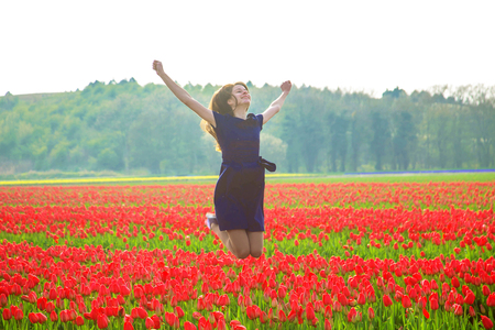 Happy young teen girl jumping up against a background of a blooming spring tulip field. Joy, youth, happiness, spring, flowering concept. Happy blooming young girl teenager. Standard-Bild - 99996170