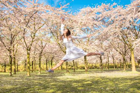 Glücklicher Jugendlicher lacht und springt . Teen Mädchen im Frühjahr Garten . Jugendlicher und Kirschblüte . Frühling und Jugend-Konzept Standard-Bild - 99973494