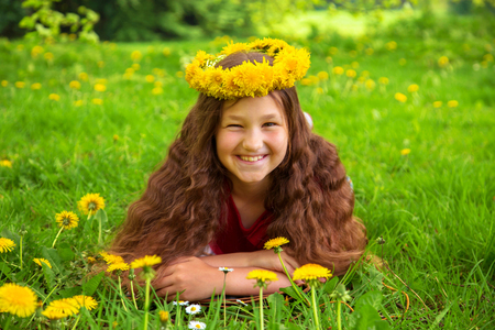 Summer portrait of a merry child. Smiling girl with long brown hair dressed in a crown of dandelions flowers. Pre-teen girl lies on the green grass on the lawn among the dandelions and laughs. Standard-Bild - 100401813