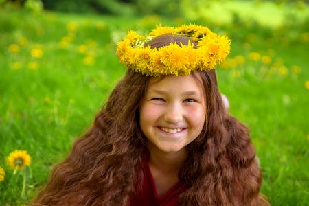 Summer portrait of a merry child. Smiling girl with long brown hair dressed in a crown of dandelions flowers. Pre-teen girl lies on the green grass on the lawn among the dandelions and laughs. Standard-Bild - 100479314