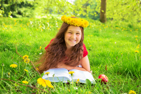 Summer portrait, merry child among the dandelions. Smiling girl with crown of dandelions flowers lies on the green grass on the lawn.  Child reads thick book with a red apple. Soon back to school! Standard-Bild - 100428520
