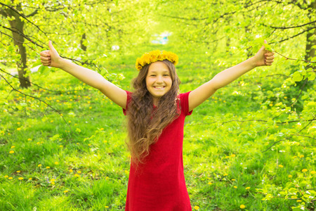 Little girl in red dress and crown of dandelions showing thumbs up symbol. Smiling child gives thumbs up gesture. Joy, success, achievements, vacations, holidays concept. Standard-Bild - 100633644