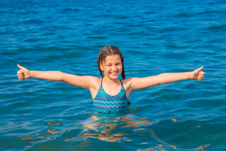 Cheerful girl swims in the sea. Child shows thumbs up sign. Smiling girl likes the sea and the beach. Happy summer holiday, summer vacation concept. Summer fun. Standard-Bild - 101341625