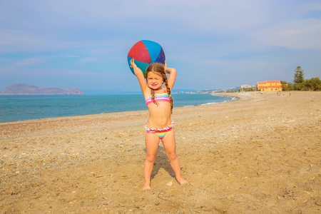 Little girl with pigtails playing ball on the sea beach. The child is happy and enjoys the summer holidays. Summer vacation, summer fun.