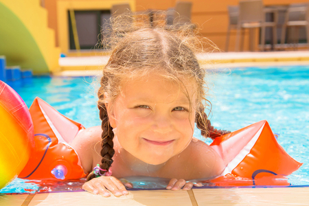 Little girl is swimming in the pool. Smiling little child dressed in swim band armlets. Summer vacation, summer fun, summer holidays. Standard-Bild - 101854790