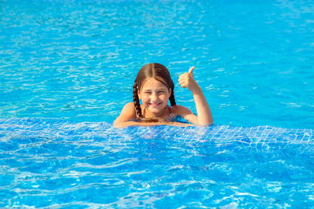 Kid swims in the pool. Smiling child leads a healthy lifestyle and keen on sports. Child shows thumb up symbol. Summer holidays, childrens swimming, summer vacation concept.