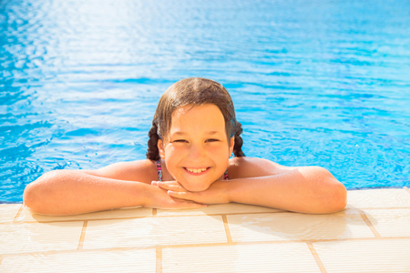 Kid swims in the pool. Smiling child leads a healthy lifestyle and keen on sports. Summer holidays, children's swimming, summer vacation concept. Standard-Bild - 102133356