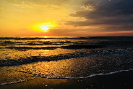 Sunset on the beach. The sun sets in the sea. Sunset on the North Sea coast. Bright sunset golden waves. Standard-Bild - 102770446