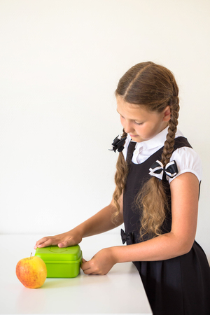 Little girl dressed in school uniform collects lunch for school in the kitchen. Child closes the lunchbox. Next to the lunchbox is an apple. Kid is ready for school. Back to school. Standard-Bild - 102844876