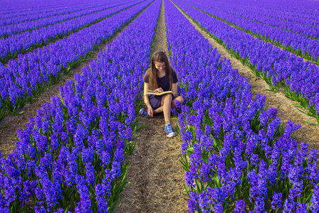 Young teen girl reads book. Teenager with book resting in flower field. Spring, education, youth, summer, back to school concept. Girl preparing to take the entrance exams to the university. Standard-Bild - 104421226
