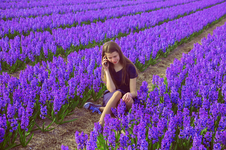 Teen girl talking on cell phone. Teenager sits in blooming field. Teen girl using telephone during the holidays. Dependence on gadgets concept. The importance of phones and friends opinions for teens. Standard-Bild - 104421227