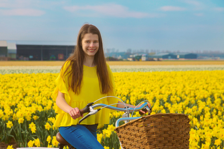 Teen girl rides a bicycle to school. Back to school concept. A teenage girl goes to college or university on a bicycle. Young people use environmentally friendly transportation. Standard-Bild - 104421228