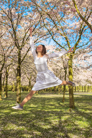 Happy teenager is laughing and jumping up. Teen girl in spring blossoming garden. Teenager and blossoming cherry blossoms. Spring and youth concept. Standard-Bild - 104421230