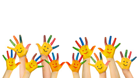 Group of happy children raises hands up. Children's hands with painted colorful palms and painted smiling faces. Joy, success, school, education, happy childhood concept. Isolated on white background.