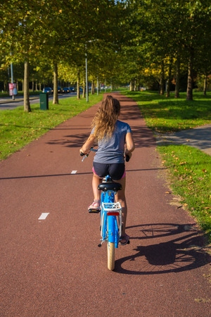 Child rides a bike on bike path. Cyclist child or teenager girl enjoys good weather and cycling. Environmentally friendly transport concept. Teen is happy. Developed cycle infrastructure. Netherlands