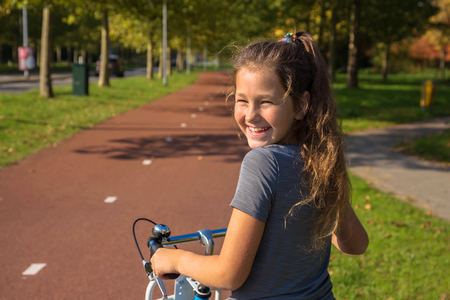 Happy child rides a bike on bike path. Cyclist child or teenager girl enjoys good weather and cycling. Environmentally friendly transport concept. Girl is smiling and laughs. Netherlands, Holland. Banque d'images