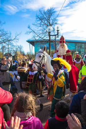 November 18, Hoofddorp, the Netherlands. The arrival of St. Nicholas Sinterklaas. Sinterklaas (Saint Nicholas) arrives with his assistants Zwarte Pieten (Black Pete). Sinterklaas rides his white horse along with his assistants. Everyone sings songs. Stockfoto - 117054325