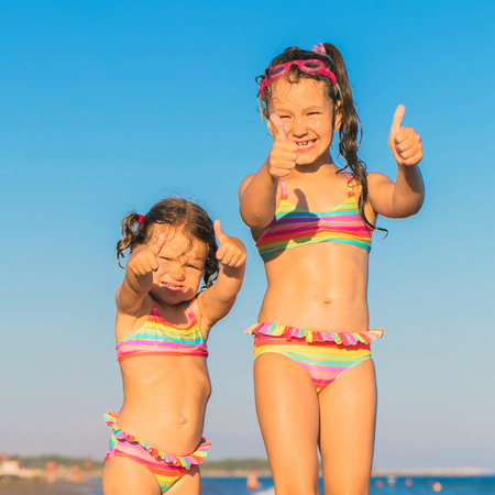 Children show thumbs up on the beach. Have fun and summer vacation concept.