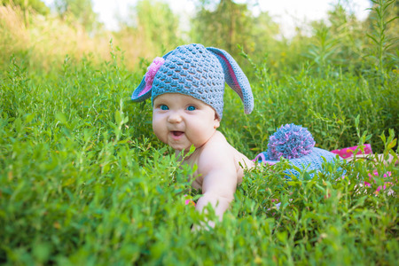 Cute baby in a Easter bunny of lamb costume in the green spring grass. Smiling baby kid posing like an Easter bunny. Children have fun.