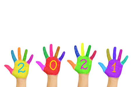 The number 2021 written on the brightly painted hands. New Year and holiday concept. Colorful palms, people are celebrating holidays. Isolated on a white background. Archivio Fotografico