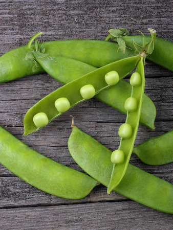 broad: Broad beans of peas on old wood background Stock Photo