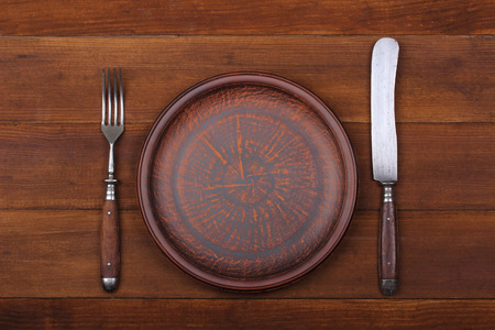 Fork, knife and dinner plate  on a brown wood background