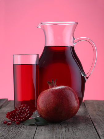Glass and jar of pomegranate juice with fruit on pink background