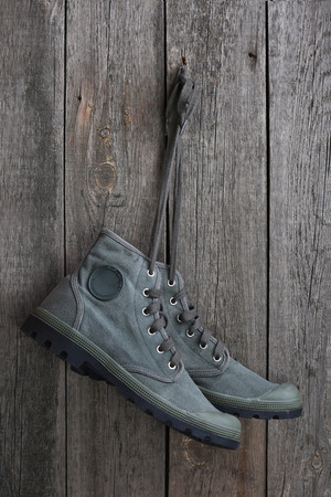 Green military sneakers hanging on a wooden wall Stock Photo