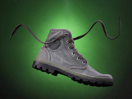 Green military style sneaker on green gradient background