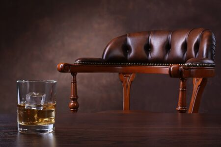 Vintage chair and glass of whiskey on wooden table over brown background Banque d'images