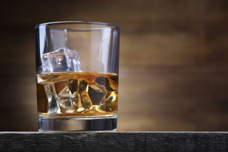 Glass with whiskey and ice cubes on brown background Banque d'images