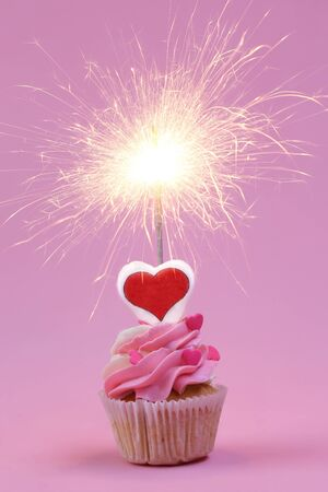 Cupcake with sparkler on pink background. Closeup Stockfoto