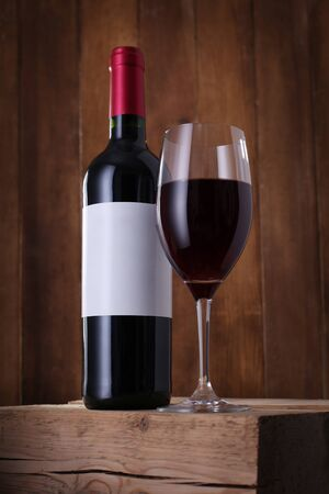 Bottle of red wine with label and wineglass on old wooden background
