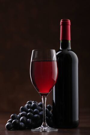 Bottle of red wine with glass and ripe grapes on brown background 写真素材