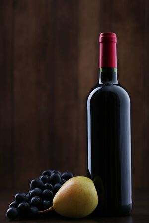 Bottle of red wine with grapes and pear on wooden background