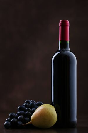 Bottle of red  wine with grapes and pear on brown background