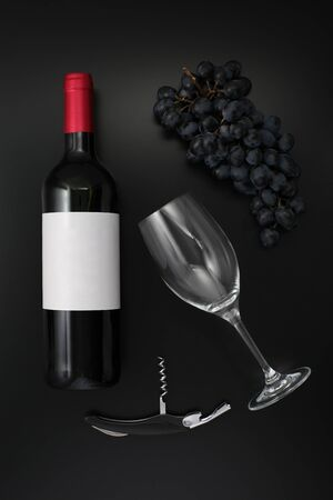 Bottle of red wine with label with glass and ripe grapes on black. Top view