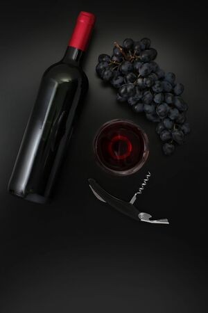Bottle of red wine, corkscrew  and ripe grapes on black background. Top view