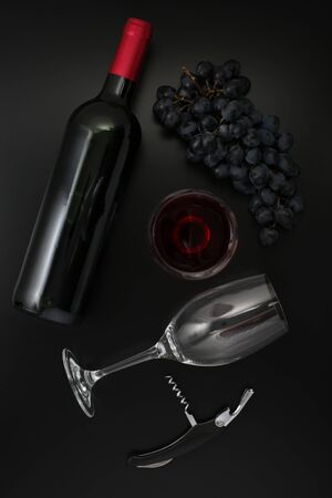 Bottle of red wine, glass, corkscrew  and ripe grapes on black background. Top view