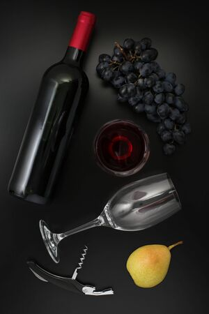 Bottle of red wine, glass, corkscrew, pear  and ripe grapes on black background. Top view