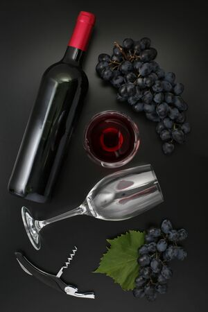 Bottle of red wine, glass, corkscrew  and ripe grapes on black background. Top view 写真素材