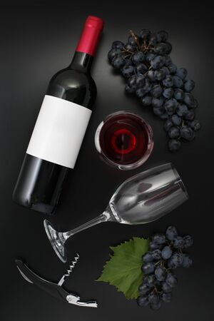 Bottle of red wine with label, glass and ripe grapes on black. Top view